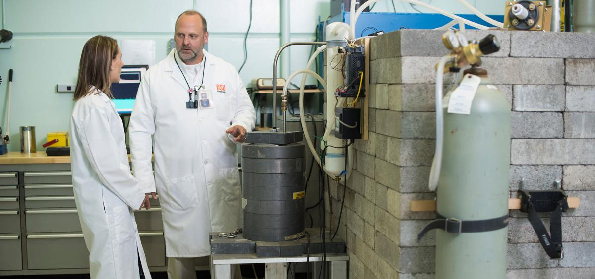 Associate Professor Steven Reese (right) works with graduate student Jessica Curtis in the reactor bay.